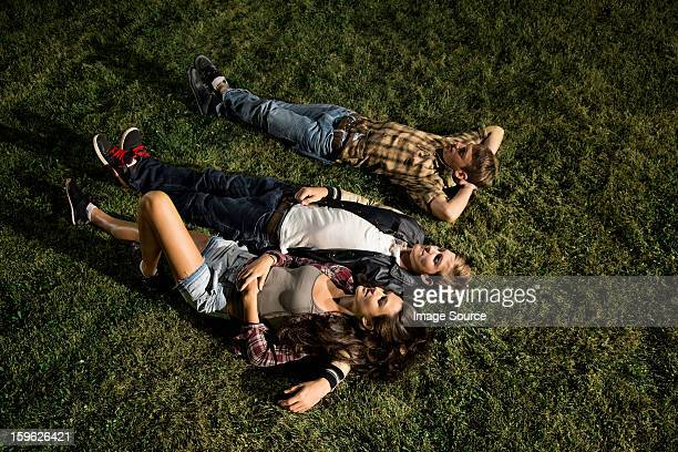 Couple and friend lying on grass at night, high angle