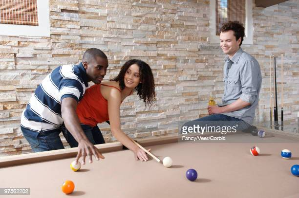 Couple and friend playing pool