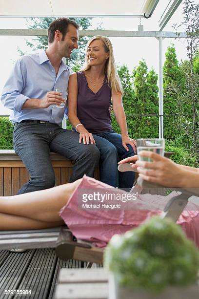 Couple and Friend Relaxing on Backyard Patio