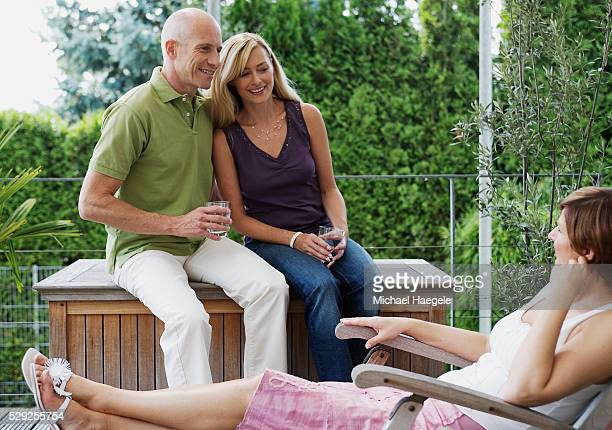 Couple and Friend Relaxing on Patio