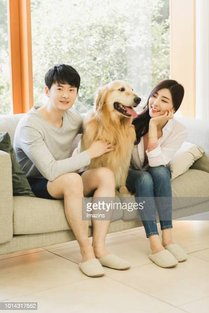 Couple and Golden Retriever sitting on sofa