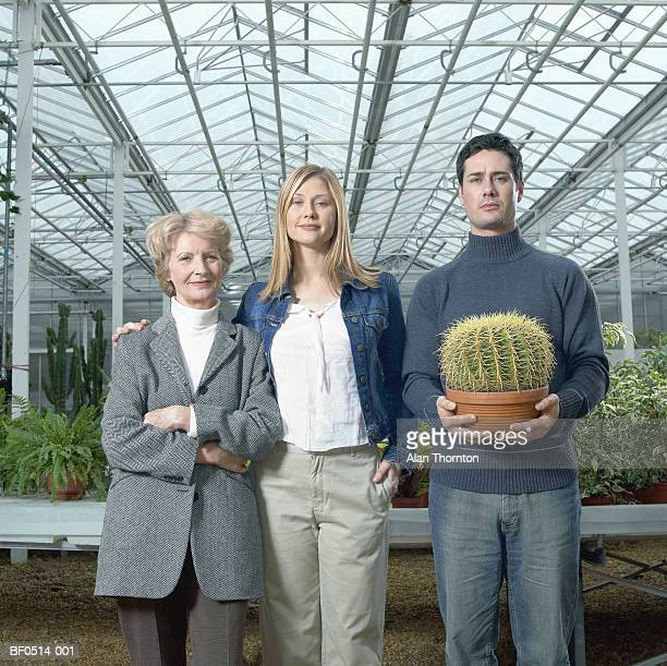 couple and mature woman in greenhouse, man holding cactus - mock turtleneck stock pictures, royalty-free photos & images