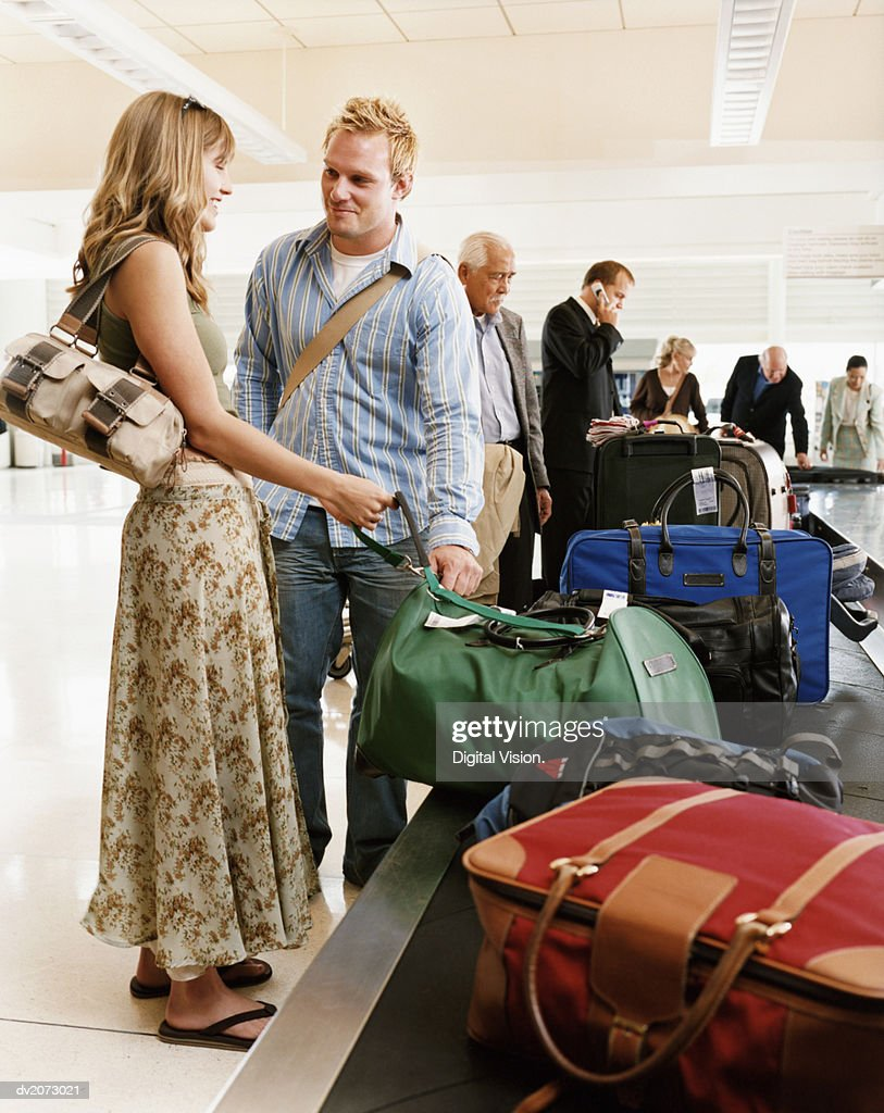 Couple and Passengers Collecting Luggage at an Airport Baggage Collection : Stock Photo