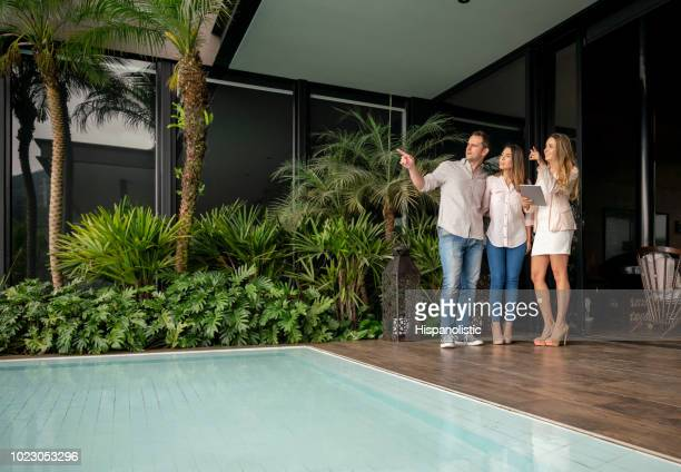 Couple and real estate agent looking at a luxury property all looking very happy