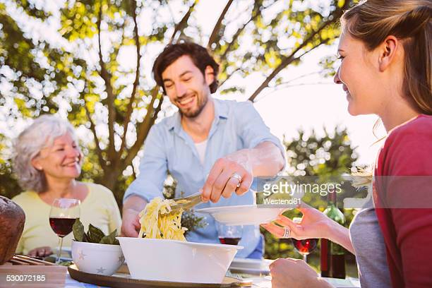 couple and senior woman having dinner in garden - mother in law stock pictures, royalty-free photos & images
