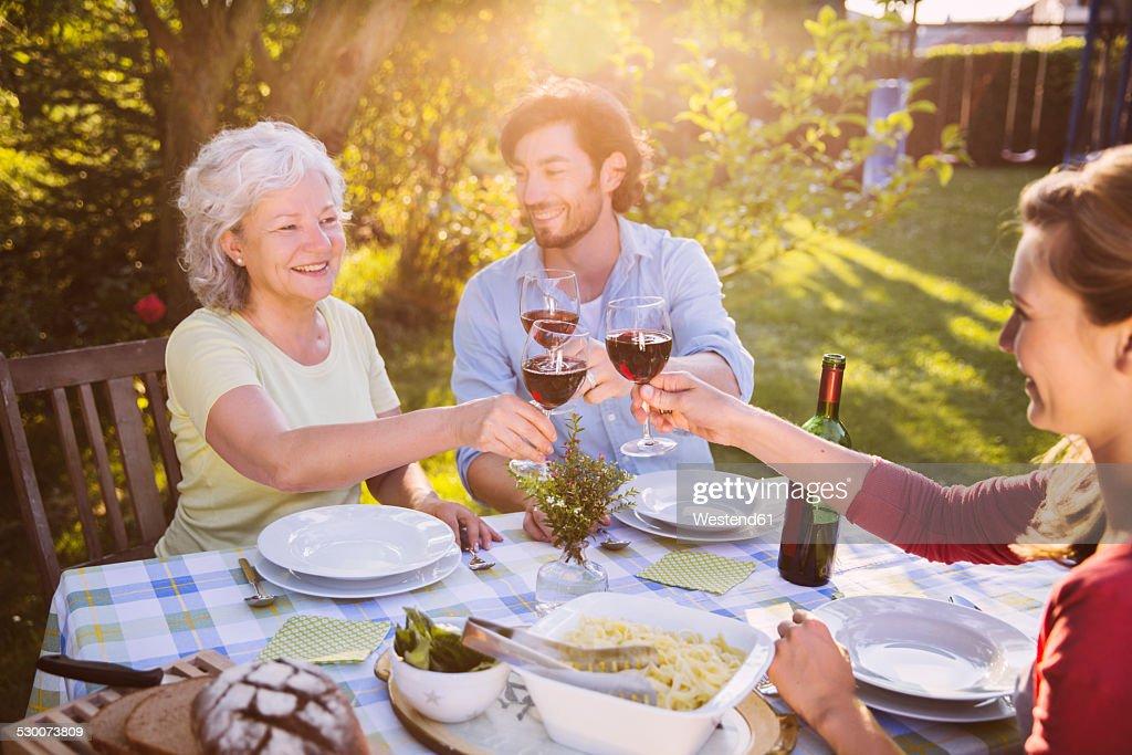 Couple and senior woman having dinner in garden : Stock Photo