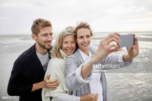 Couple and senior woman taking selfie on the beach