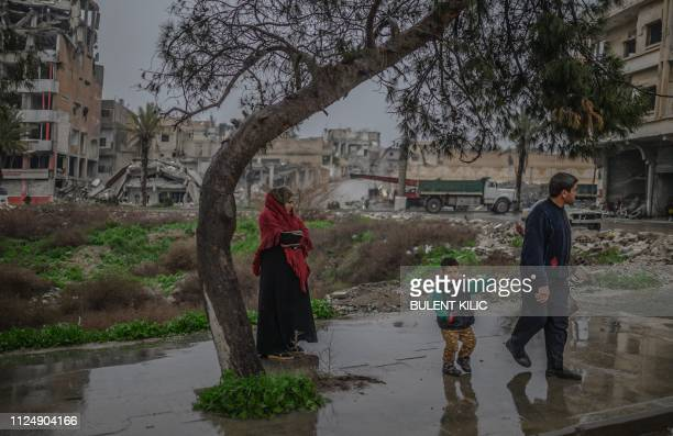 TOPSHOT A couple and their child wait to cross a street in the northern Syrian city of Raqa on February 14 2019 In 2014 jihadists of the Islamic...