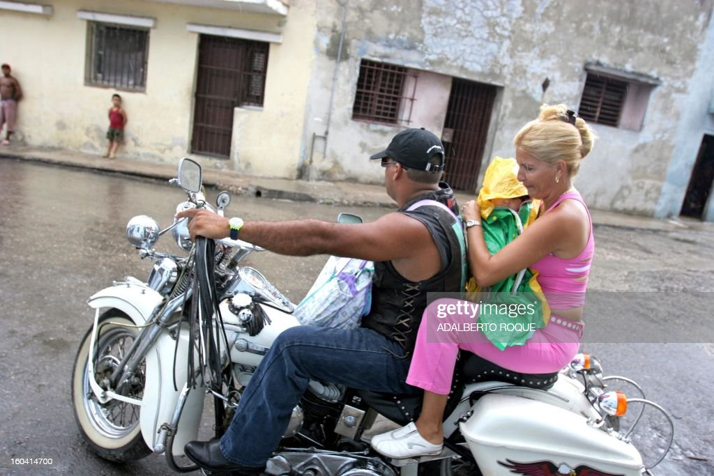 A couple and their daughter ride a 1939 45 Twin-WLD Harley-Davidson along Luyano neighbourhood in Havana,19 June 2005. Though Cuban customs laws prohibit their exportation, foreigners who highly covet these classics can pay between 5,000 and 15,000 US dollars for each of the twenty English motorbikes - Triumph, Norton and Ariel, and the more than a hundred US Harley-Davidsons that ride through the island's streets. These Harley-Davidsons arrived in the country between 1925 and 1960, year in which the last US lot was sent for the police mobile units. Due to the US 44-year embargo to Cuba, mechanics have been adapting parts of cars from the former Soviet Union, to counteract the lack of original Harley-Davidson pieces. AFP PHOTO/Adalberto ROQUE /