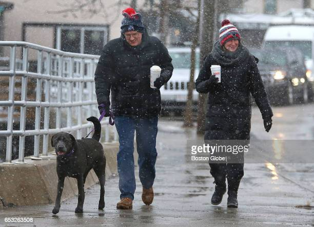 A couple and their dog make their way along the Scituate Waterfront while snow and sleet blow sideways as a winter storm arrives in the region on Mar...