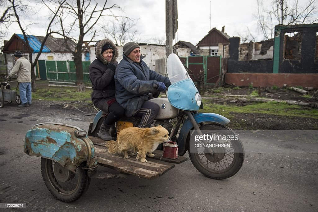 A couple and their dog ride a motorbike with a side-car in the village of Nikishino on April 21, 2015 in the self-proclaimed Donetsk People's Republic (DNR). Only a handful stayed during the fighting here and as people returned to the village counting some 450 houses they found some 240 of those reduced to rubble or had been destroyed beyond repair. The lack of building material and limited emergency food deliveries see mostly elderly people with no were to flee returning and sheltering in their still habitable outhouses.