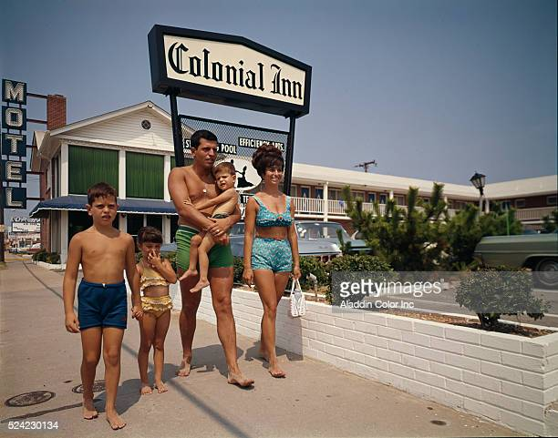 A couple and their three children walk barefoot past the Colonial Inn in Virginia Beach | Location Virginia Beach City Virginia USA