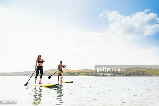 Couple and toddler daughter standup paddleboarding on tranquil sea, Carlsbad, California, USA