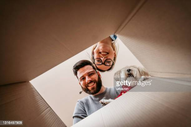 couple and toy dog unpacking cardboard box together - mail stock pictures, royalty-free photos & images