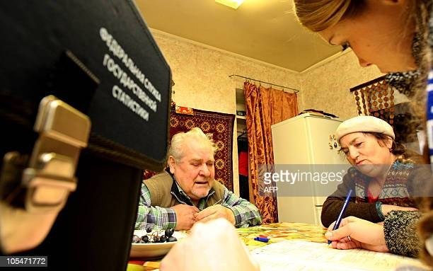 A couple answers questions of a census taker in the village of Murino near SaintPetersburg on October 14 during the first day of Russia's nationwide...