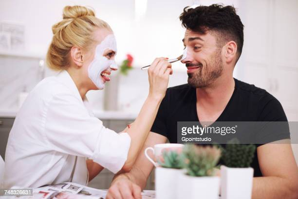 Couple applying face masks smiling