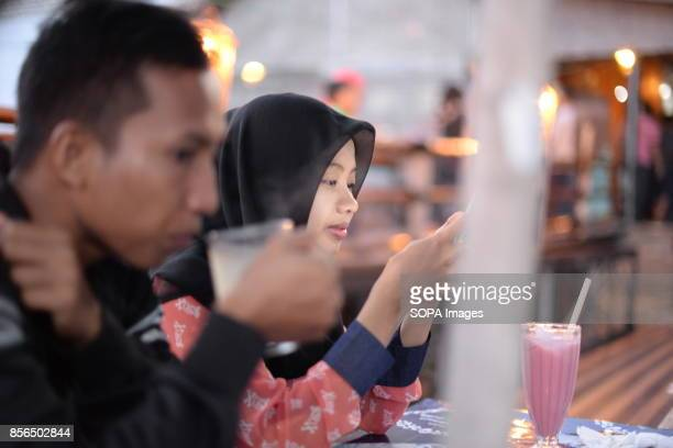 A couple are seen enjoying a smoothy drink and using Wifi internet in a Warkop in Madura Island 'Warkop' is the name of Indonesia small cafeterias...