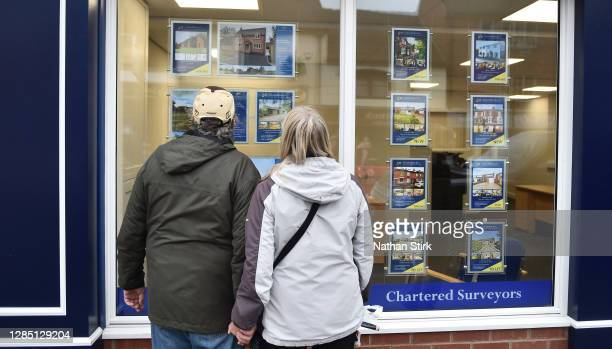 Couple are seen looking at houses for sale at an estate agents in Market Town of Leek on November 11, 2020 in Leek, England. The United Kingdom will...