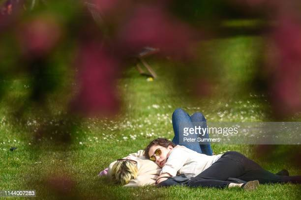 A couple are seen lying on each other while relaxing in the sunshine St James's Park on May 15 2019 in London England Forecasters are predicting days...