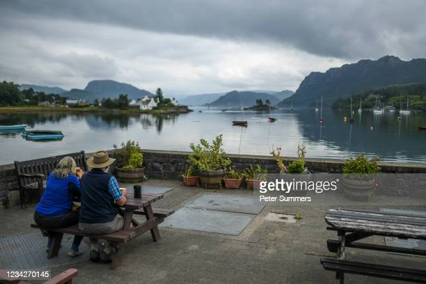 Couple are seen sat at a table on July 27, 2021 in Plockton, Scotland. Skye and Raasay attracted 650,000 visitors in pre-covid 2019 with a combined...