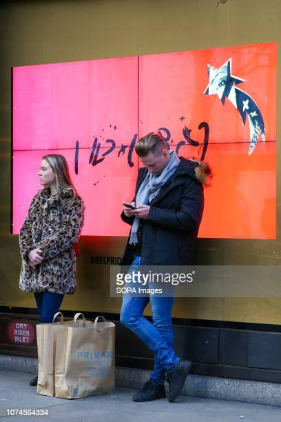 A couple are seen with shopping bags standing next to a festive window display on London's Oxford Street with 3 days to Christmas Day Retailers are...