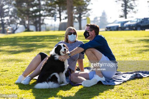 Couple are seen with their dog at City Beach foreshore on April 25, 2021 in Perth, Australia. Lockdown restrictions remain in place across the Perth...