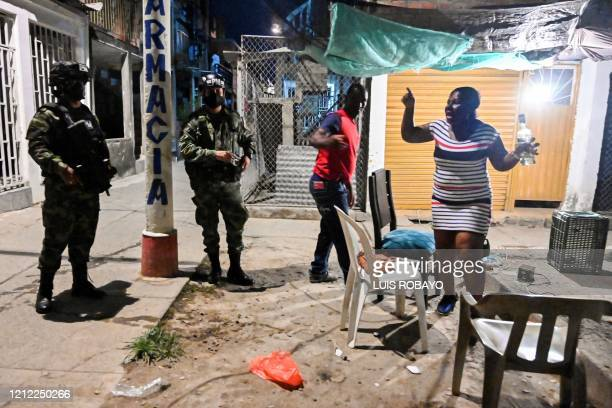 Couple argue with Colombian soldiers after being caught violating the curfew in Cali, Colombia on May 8, 2020. - Authorities from the city of Cali...
