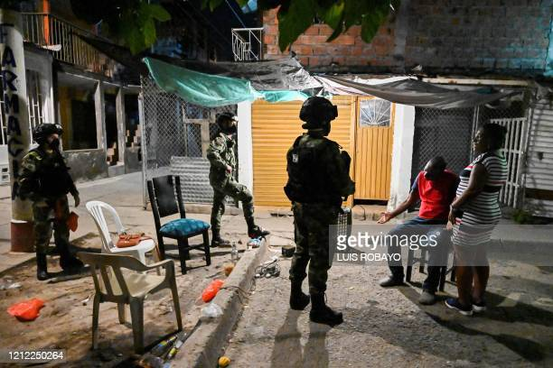 Couple argues with Colombian soldiers after being caught violating the curfew in Cali, Colombia on May 8, 2020. - Authorities from the city of Cali...