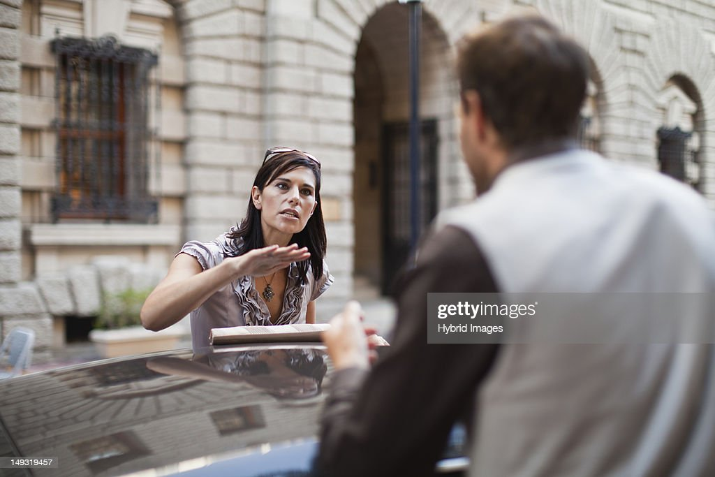 Couple arguing over sports car : Stock Photo