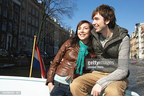 Couple arm in arm on boat on canal, smiling