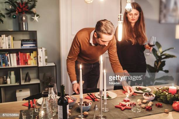 couple arranging dining table with christmas decoration