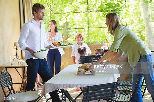 couple arranging food on dining table with family in the background - aunt - fotografias e filmes do acervo