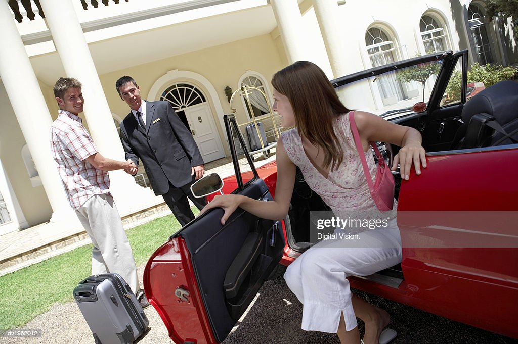 Couple Arrive at a Hotel, the Woman Alighting From a Convertible and the Man Greeting the Doorman : Stock Photo