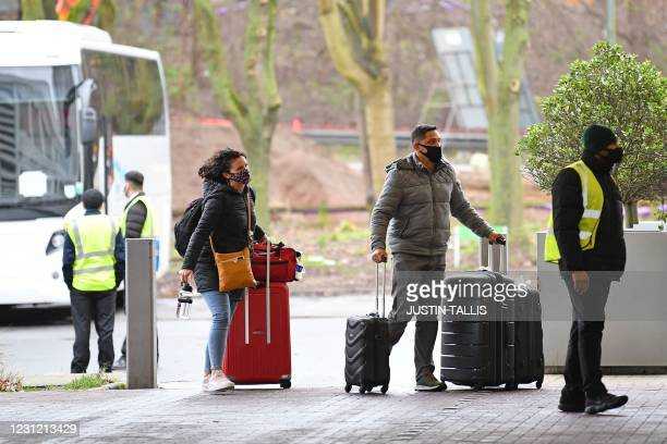 Couple arrive with their luggage by coach to the Holiday Inn hotel near Heathrow Airport in west London on February 17, 2021 where travellers are...