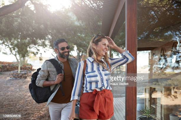 couple arriving at amazing cabin in the wild - reportage stock pictures, royalty-free photos & images