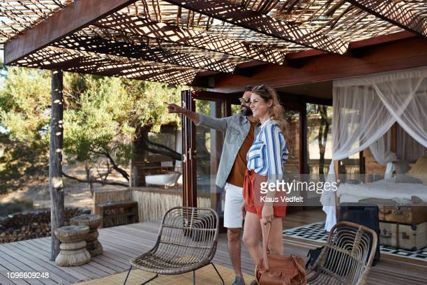 couple arriving at amazing cabin in the wild - mid adult stock pictures, royalty-free photos & images