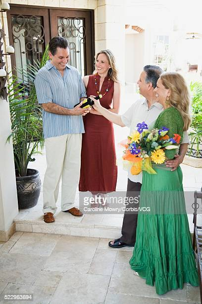couple arriving at friends' house - older women in short skirts stock pictures, royalty-free photos & images