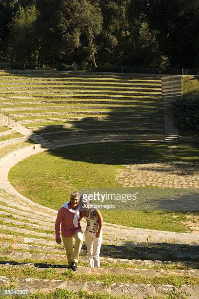 Couple ascending amphitheater steps, Florence, Italy