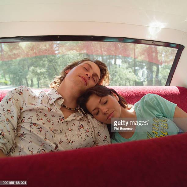 Couple asleep in back of car, woman resting head on man's shoulder