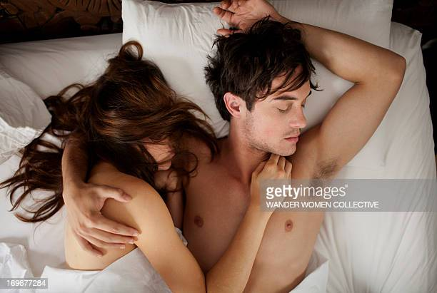 Couple asleep in bed cuddling under white sheets