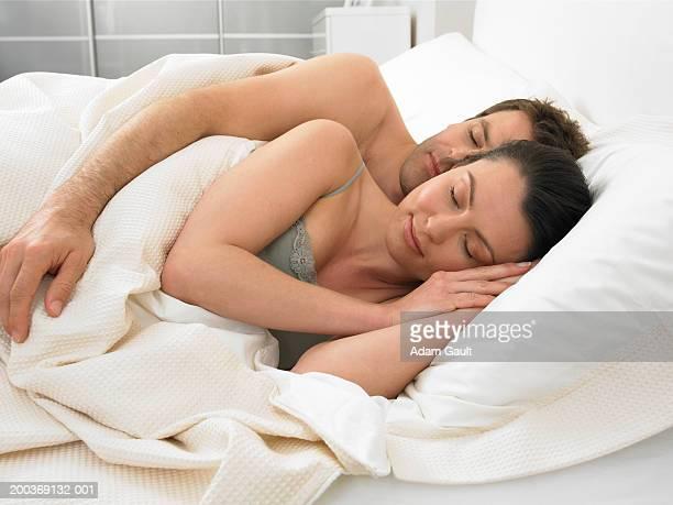 couple asleep in bed, man embracing woman - abbracciarsi a letto foto e immagini stock