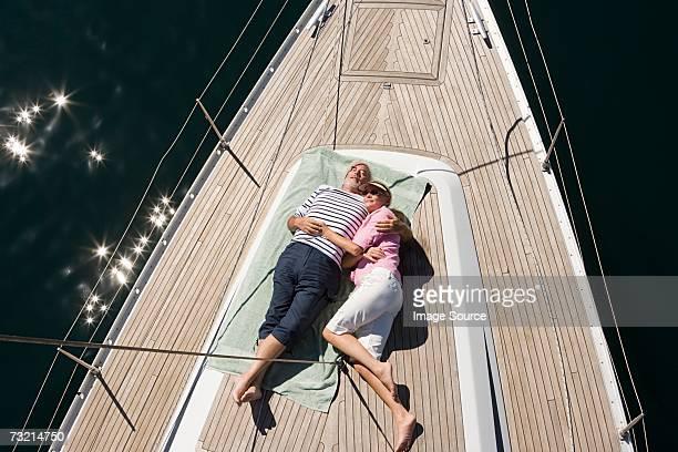 Couple asleep on deck of sailboat