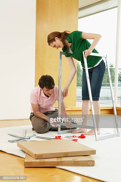 Couple assembling flat-pack furniture, woman bending over smiling