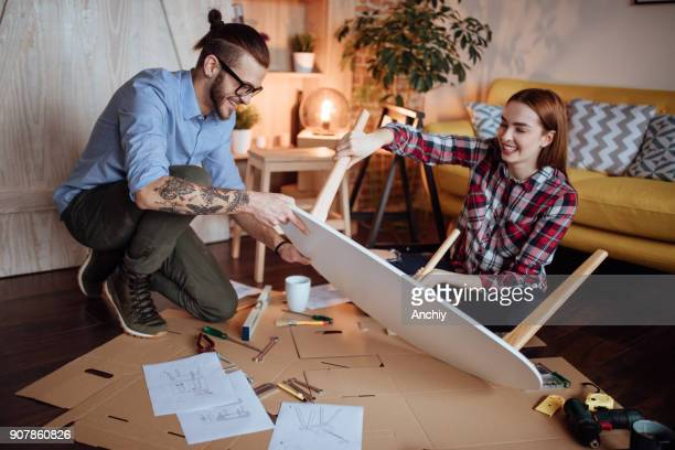 Couple assembling furniture in new house