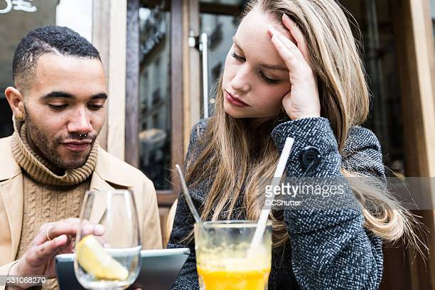 couple at a cafe with their digital tablet - paris fury stock pictures, royalty-free photos & images