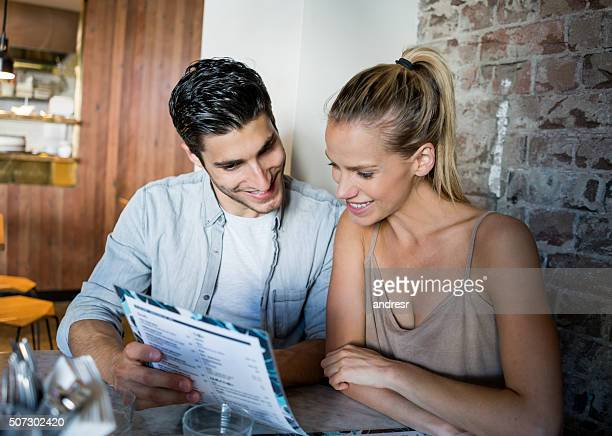 Couple at a coffee shop looking at the menu
