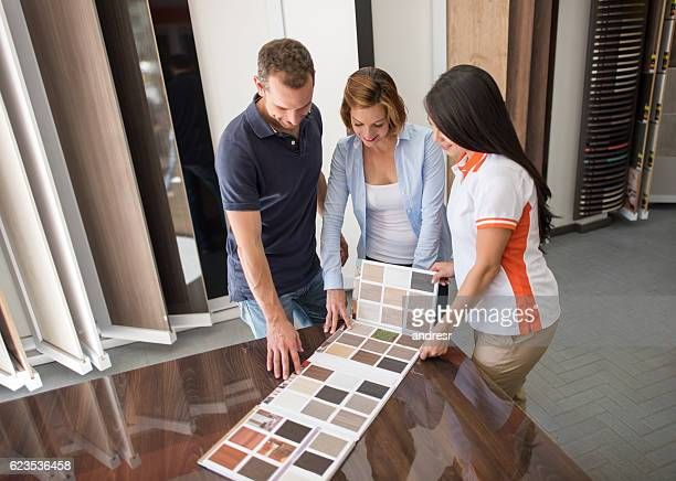 couple at a floor store looking at wood samples - pavimento di mattonelle foto e immagini stock
