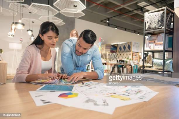 paar in einem möbelhaus eine farbpalette zu betrachten - designer einrichtung stock-fotos und bilder