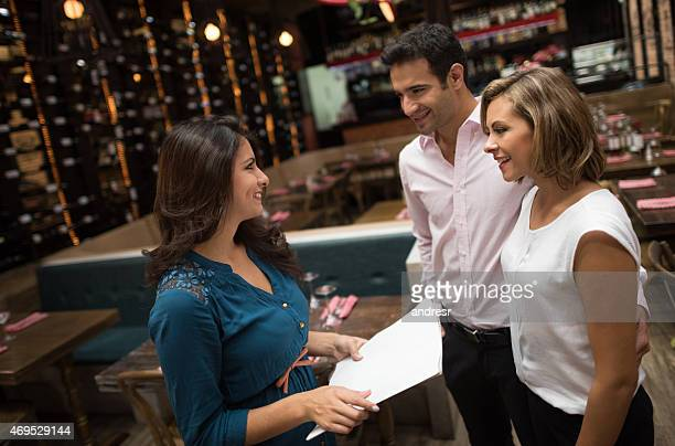 couple at a restaurant talking to the hostess - party host stock pictures, royalty-free photos & images