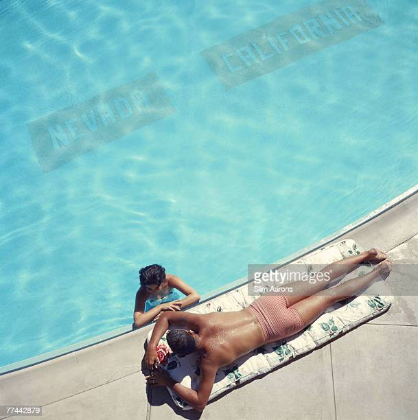 A couple at a swimming pool near Lake Tahoe California 1959 The line on the bottom of the pool marks the state line between Nevada and California